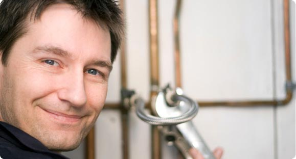 Smiling friendly plumber fixing leaking pipe